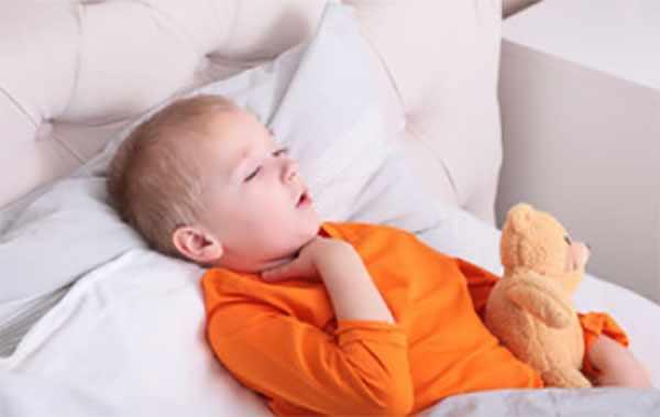Мальчик в кровати кашляет и держится за горло