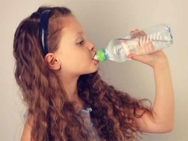 Девочка пьет воду из бутылочки