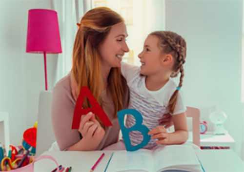 Мама с дочкой знакомятся с печатными буквами. Держат их в руках