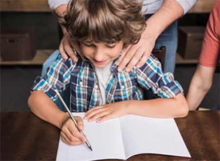 Ребенок пишет в тетради. Сзади стоят родители