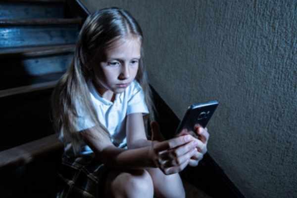 Девочка в темноте сидит на лестнице с телефоном в руках