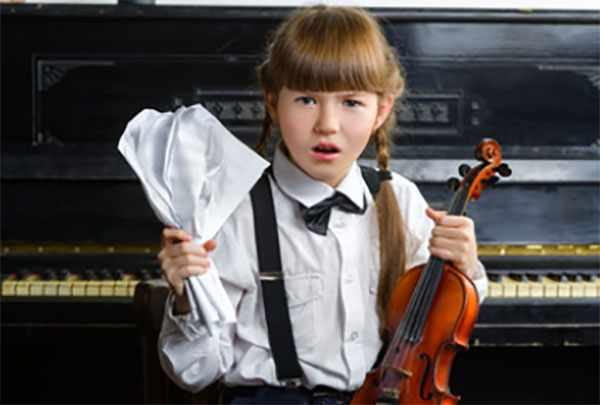 Девочка жмет в одной руке ноты, в другой - держит скрипку
