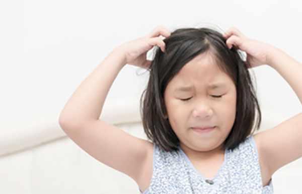 Девочка двумя руками чешет голову