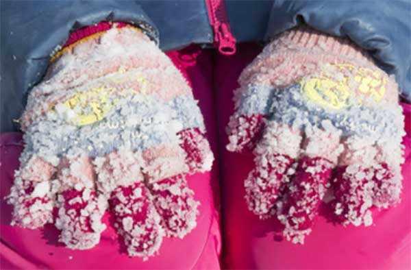 Руки ребенка в перчатках, залепленных в снегу
