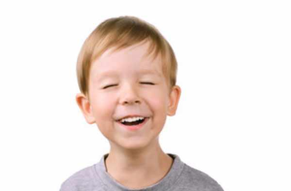 Мальчик моргает и улыбается
