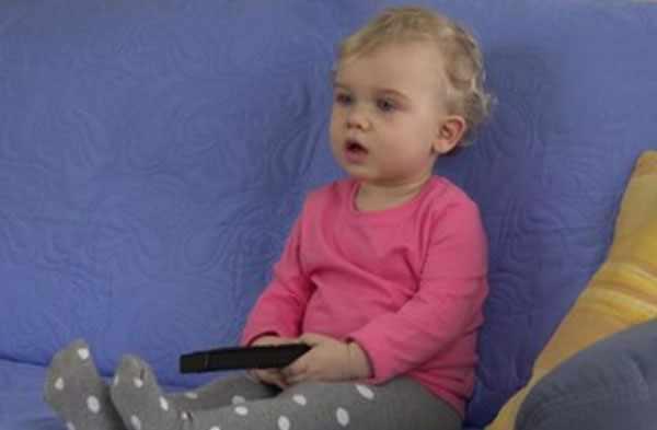 Годовалая девочка сидит с пультом от телевизора и смотрит прямо (по всей видимости на экран)