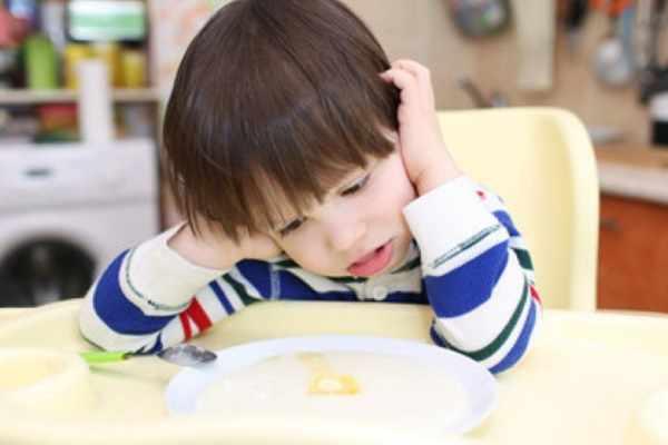 ребенок задумчиво смотрит на свою тарелку