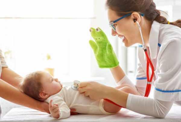 Доктор отвлекает грудного ребенка игрушкой. Слушает его грудку