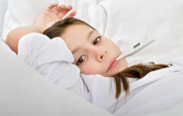 Девочка лежит с градусником во рту