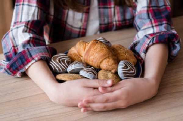 Ребенок обхватил множество сладостей