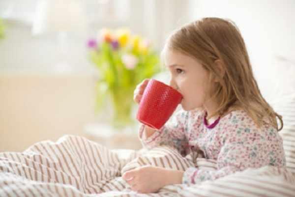 Девочка лежит в постели и пьет чай