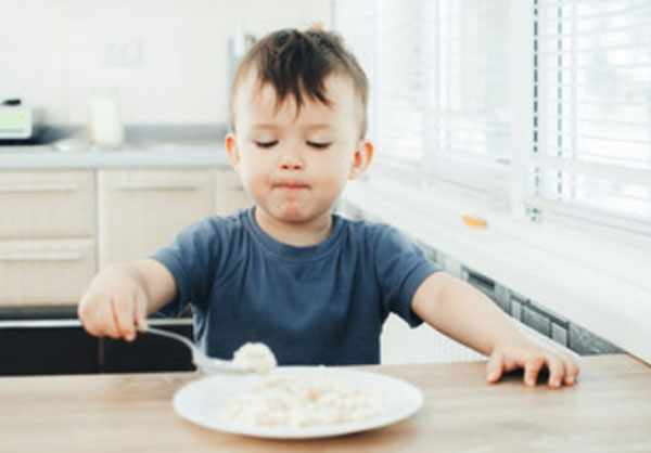 Ребенок сидит перед тарелкой разваренного риса. Набрал еду в ложку