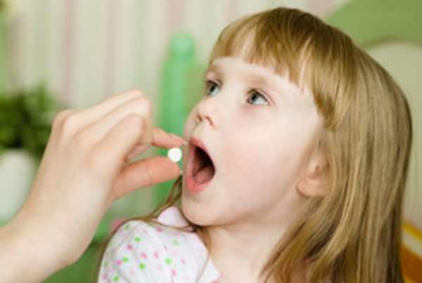 Девочке кладут в рот таблетку