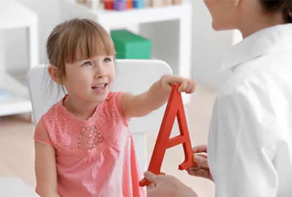 Девочка учит с мамой звукА. Перед ней пластиковая буква