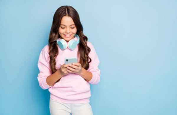 Девочка улыбается, смотря на экран телефон