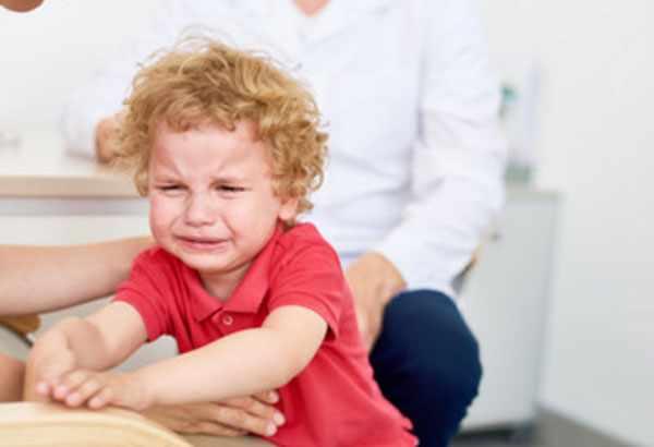 Мальчик в красной футболке всхлипывает. рядом родители