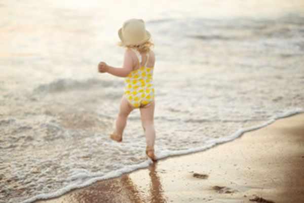 Девочка в панамке и купальнике шагает в морскую воду