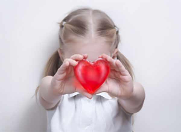 Девочка держит перед собой пластиковое сердца, ее лица не видно
