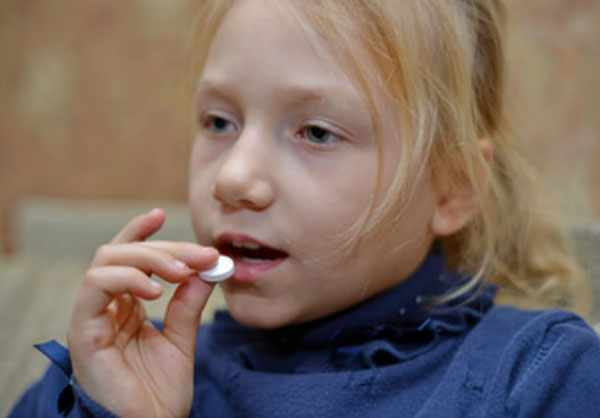 Девочка кладет в рот таблетку