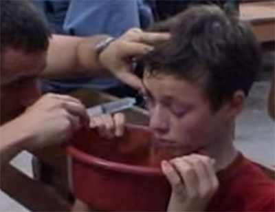Отец промывает сыну глаза. Мальчик наклонил голову над тазиком