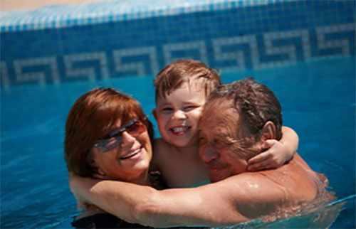 Счастливый мальчик в бассейне с бабушкой и дедушкой