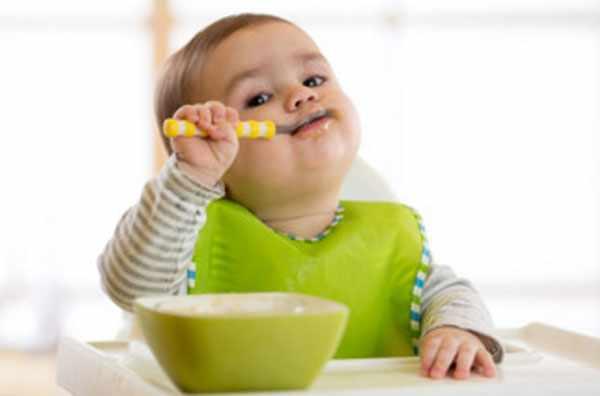 Маленький ребенок кушает с ложечки
