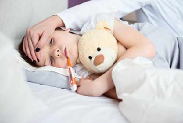 Мальчик с градусником во рту лежит в постеле. Он прижимает к себе плюшевого медведя