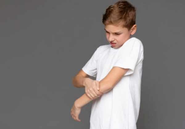 Мальчик испытывает боль. Он держится за руку