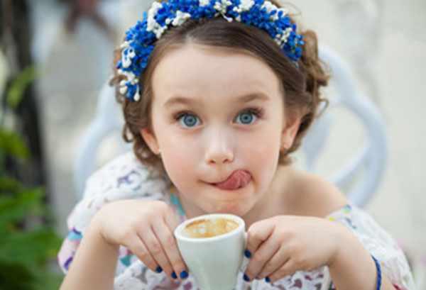 Девочка держит в руках пустую чашку от кофе и облизывается