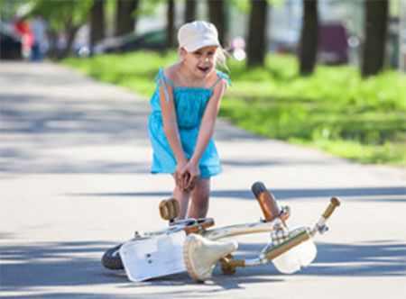 Девочка стоит возле перевернутого велосипеда и держится за коленко