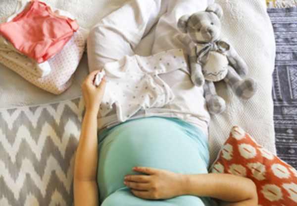 Беременная женщина с большим животом подготавливает вещи для будущего ребенка