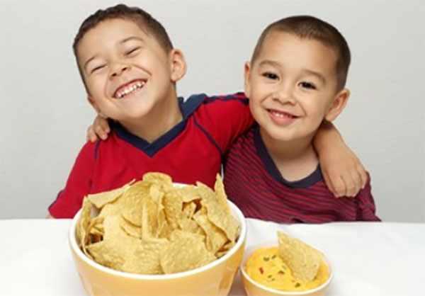 Два мальчика сидят за столом. Перед ними тарелки с чипсами