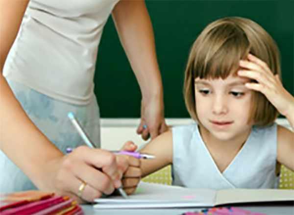 Учитель исправляет девочке в тетради ошибки