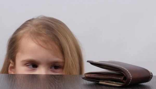 Девушка смотрит на кошелек, который лежит на тумбочке
