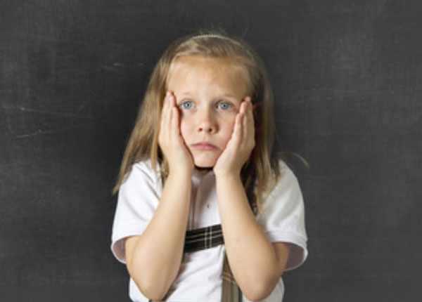 Девочка расстроена. Положила руки себе на щеки
