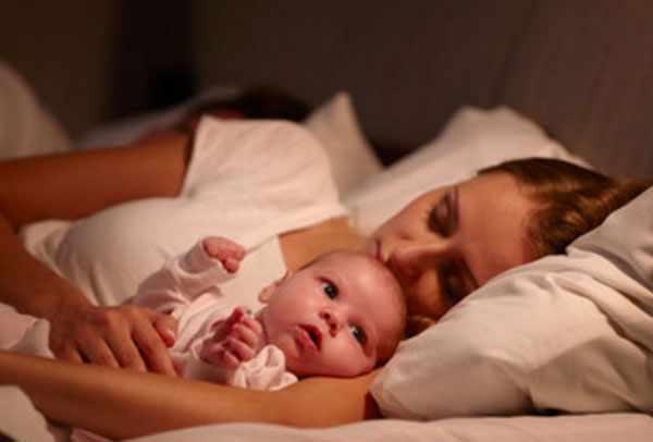 мама с грудничком в кровати. Она с закрытыми глазами, малыш - нет