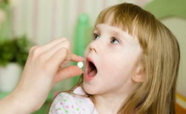 Девочка принимает таблетку