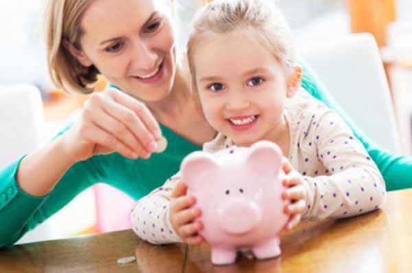 Девочка держит копилку. Мама кладет в нее монетки