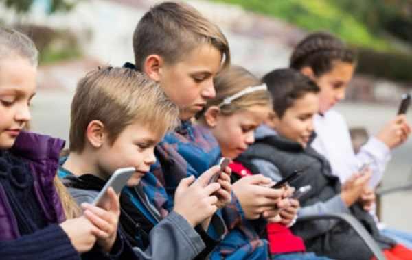 Дети сидят с телефонами в руках