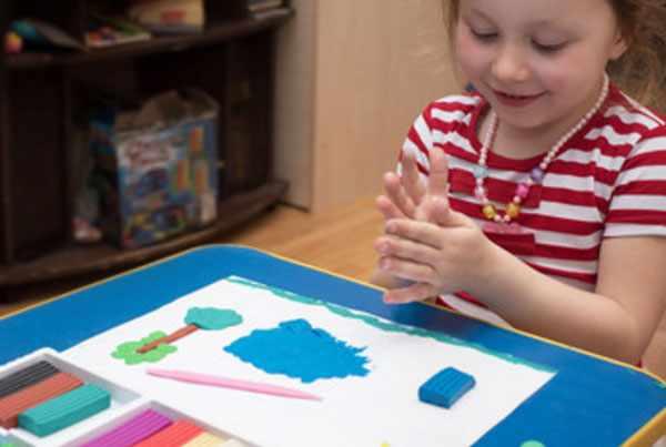 Девочка скатывает пластилин в ладошках. Перед ней лежит картина из пластилина
