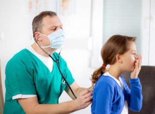 Врач прослушивает грудную клетку со спины пациентки, которая кашляет