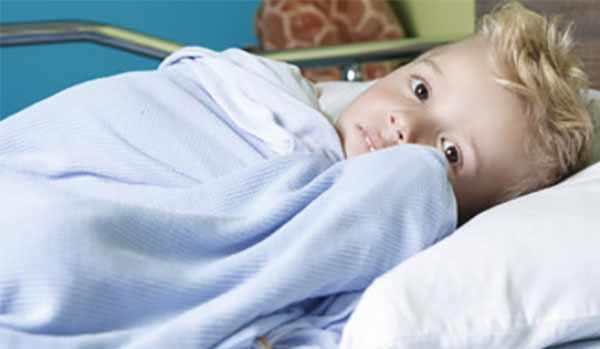 Мальчик лежит на больничной кушетке