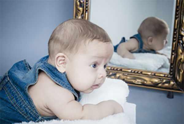 Грудной ребенок лежит возле зеркала