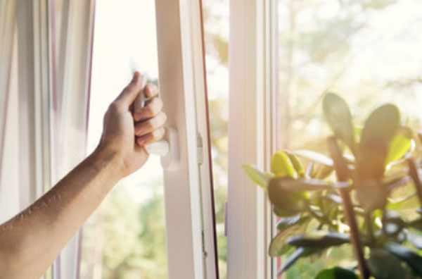 Женщина открывает окно на проветривание