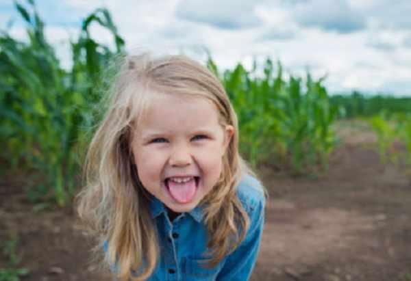 Веселая девочка показывает язык