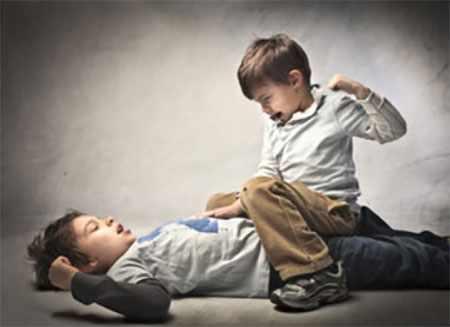 Один мальчик сидит на другом ребенке и собирается ударить его по лицу