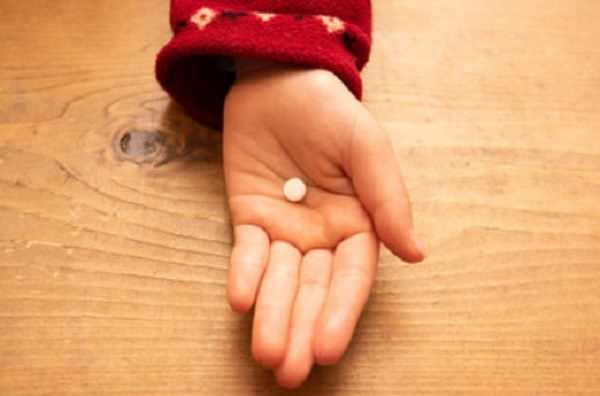 Ладонь ребенка с таблеткой