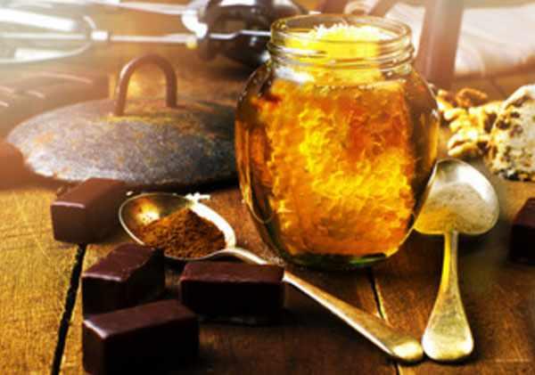 Баночка с медом. Рядом шоколадные конфетки