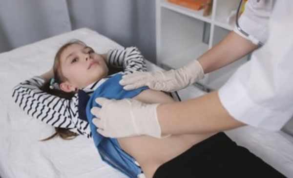 Девочка лежит на кушетке. Доктор собирается пальпировать живот