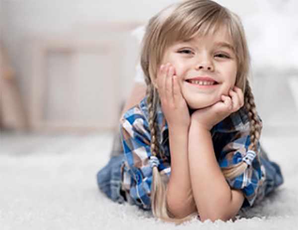 Девочка с косичками лежит на полу и загадочно улыбается